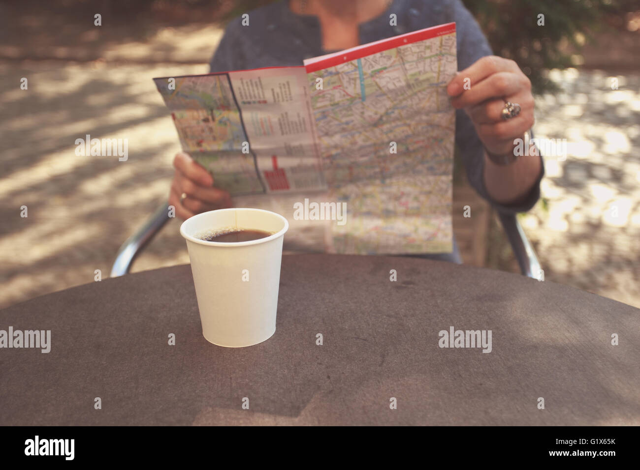 An elderly woman is sitting outside on a sunny day and is studying a city map whilst having coffee - Stock Image