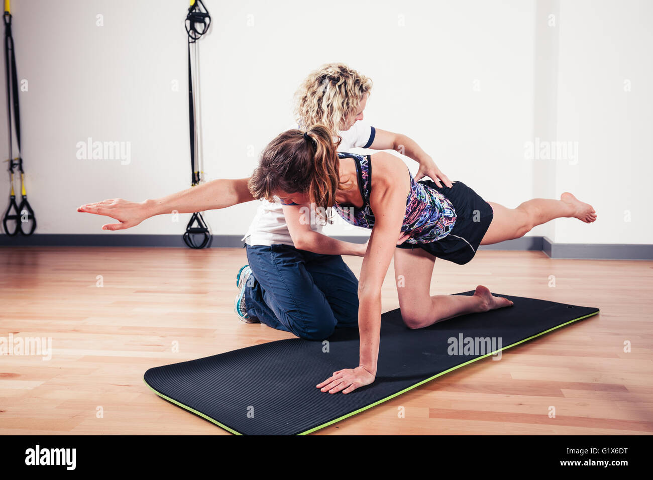 A therapist is correcting the technique of a woman exercising and stretching in a gym - Stock Image