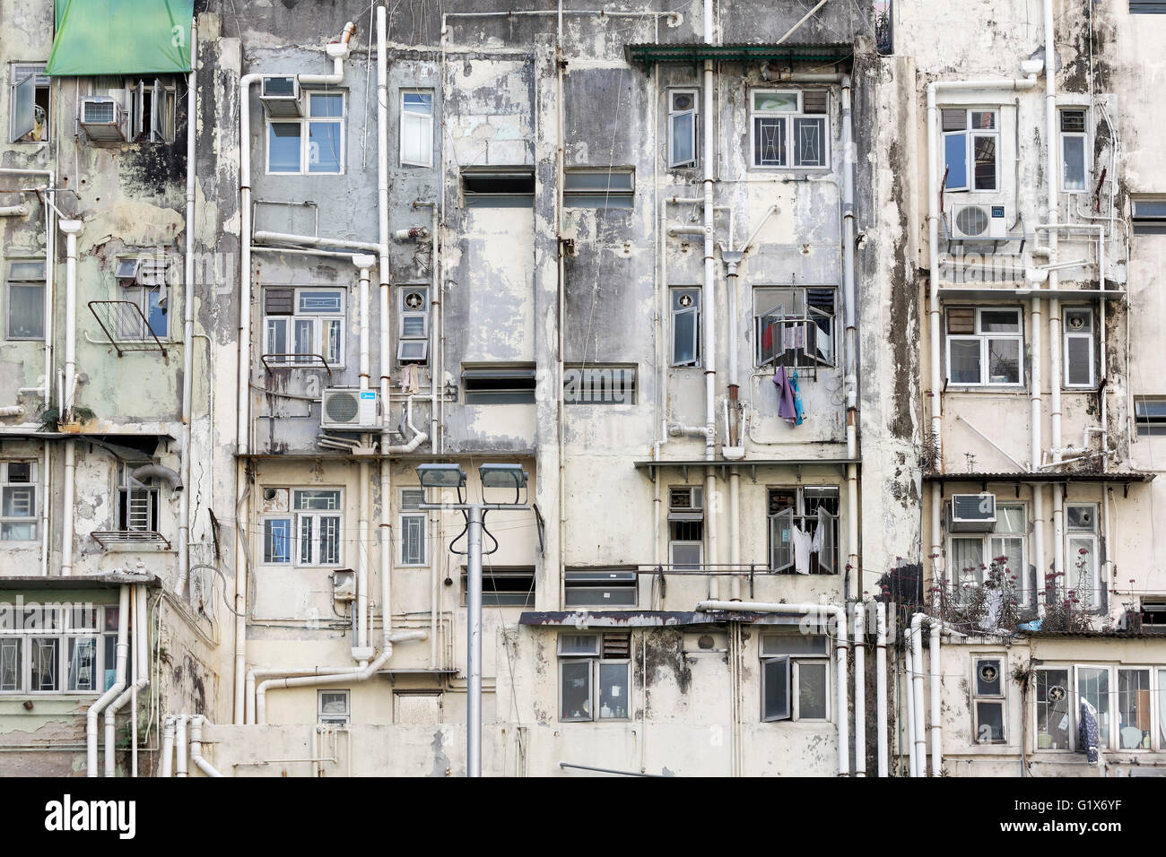 Shabby, ramshackle house facade with external drains and air conditioners, House in Victoria City, Sheung Wan, Hong - Stock Image