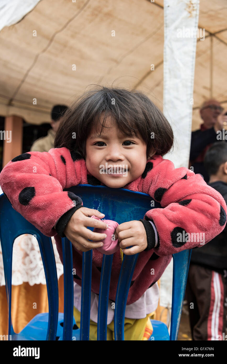 Local girl leans over chair, Luang Prabang Province, Louangphabang Province, Laos - Stock Image