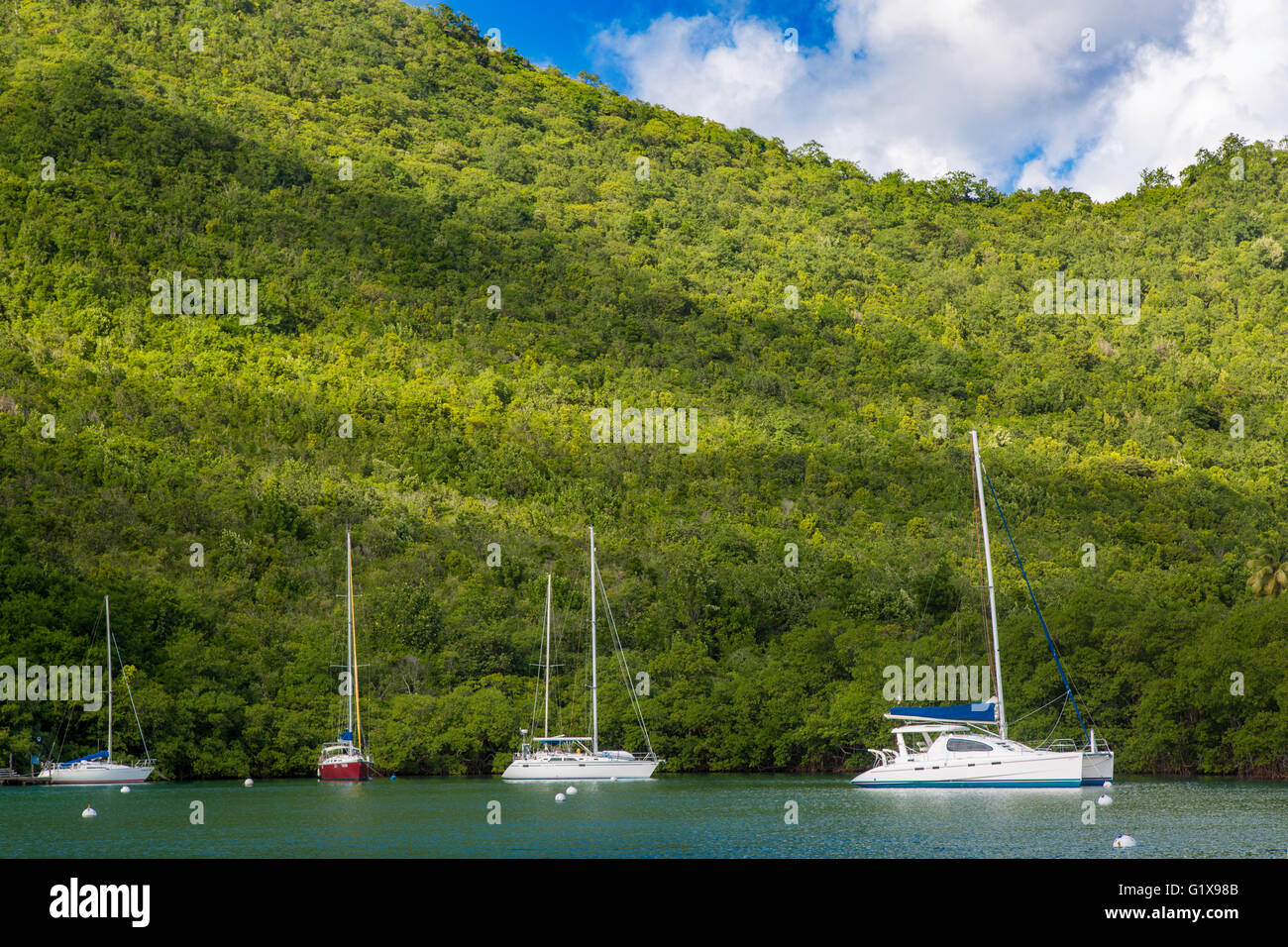 Boats moored in the tiny harbor at Marigot Bay, St. Lucia, West Indies - Stock Image
