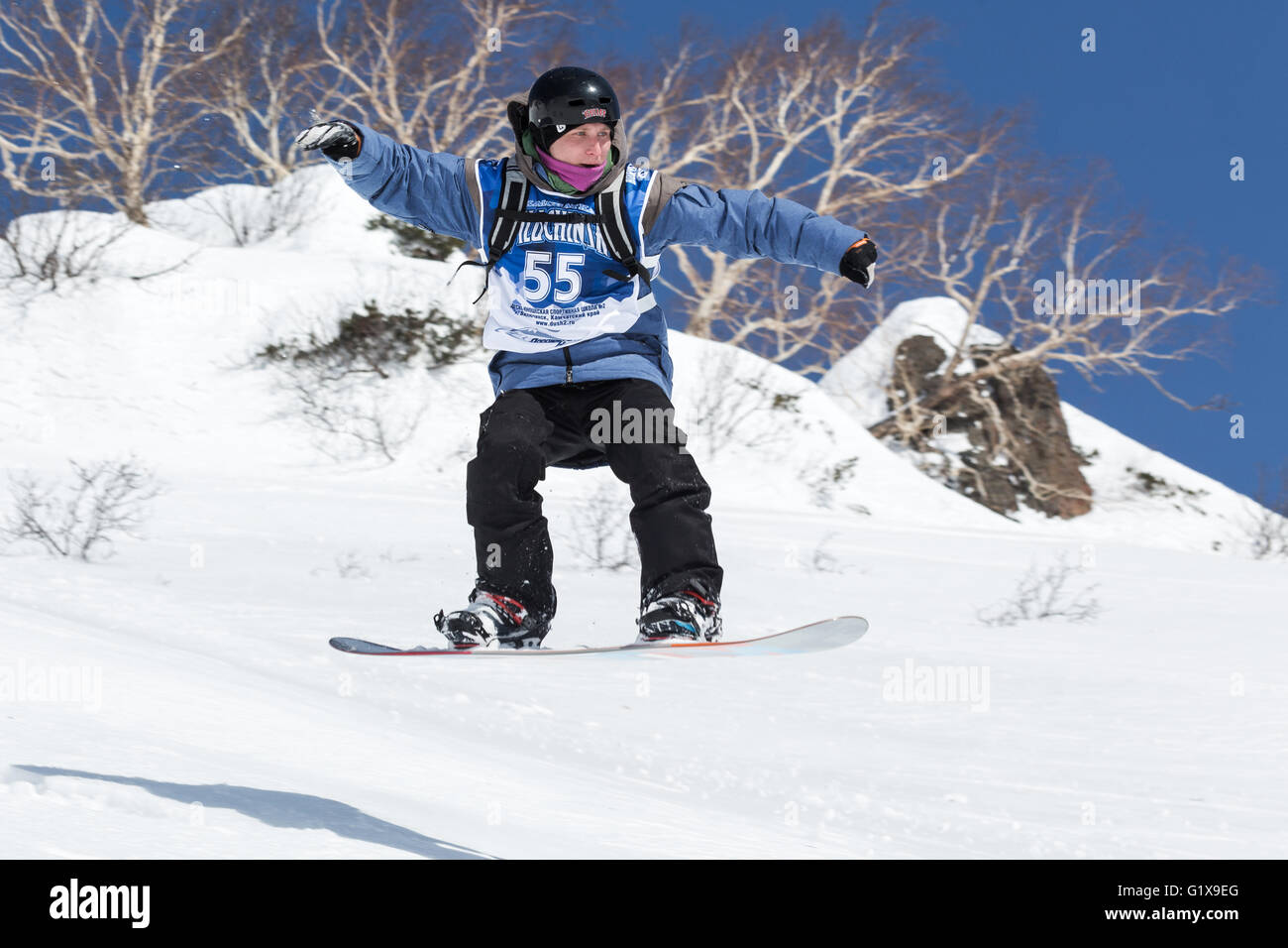 Snowboarder rides steep mountains. Competitions freeride skiers and snowboarders Kamchatka Freeride Open Cup. - Stock Image