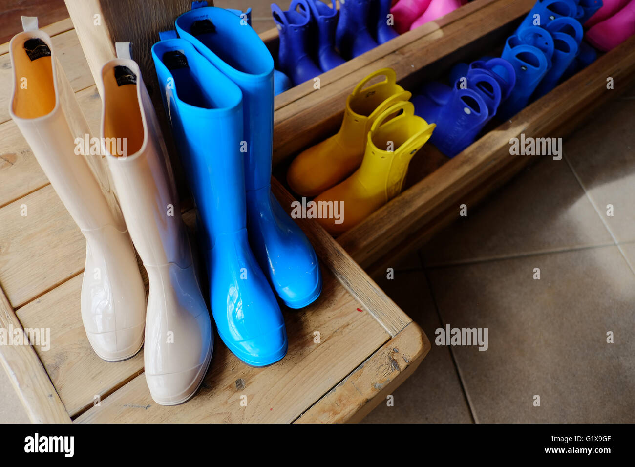 Rubber boots large and small stored in a wooden boot rack. - Stock Image