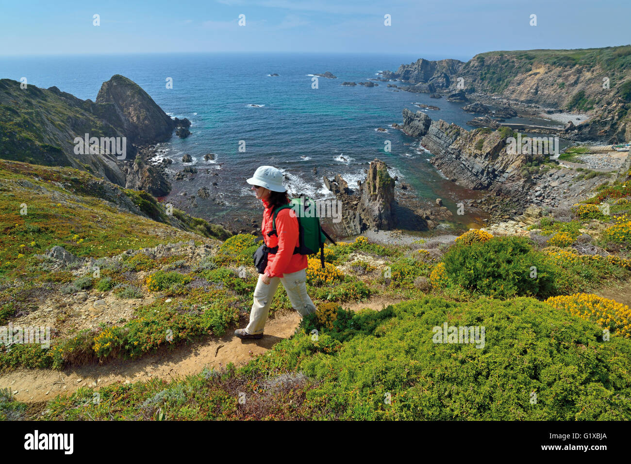 Portugal, Alentejo: Woman walking along coastal track of trekking route Rota Vicentina with ocean view - Stock Image