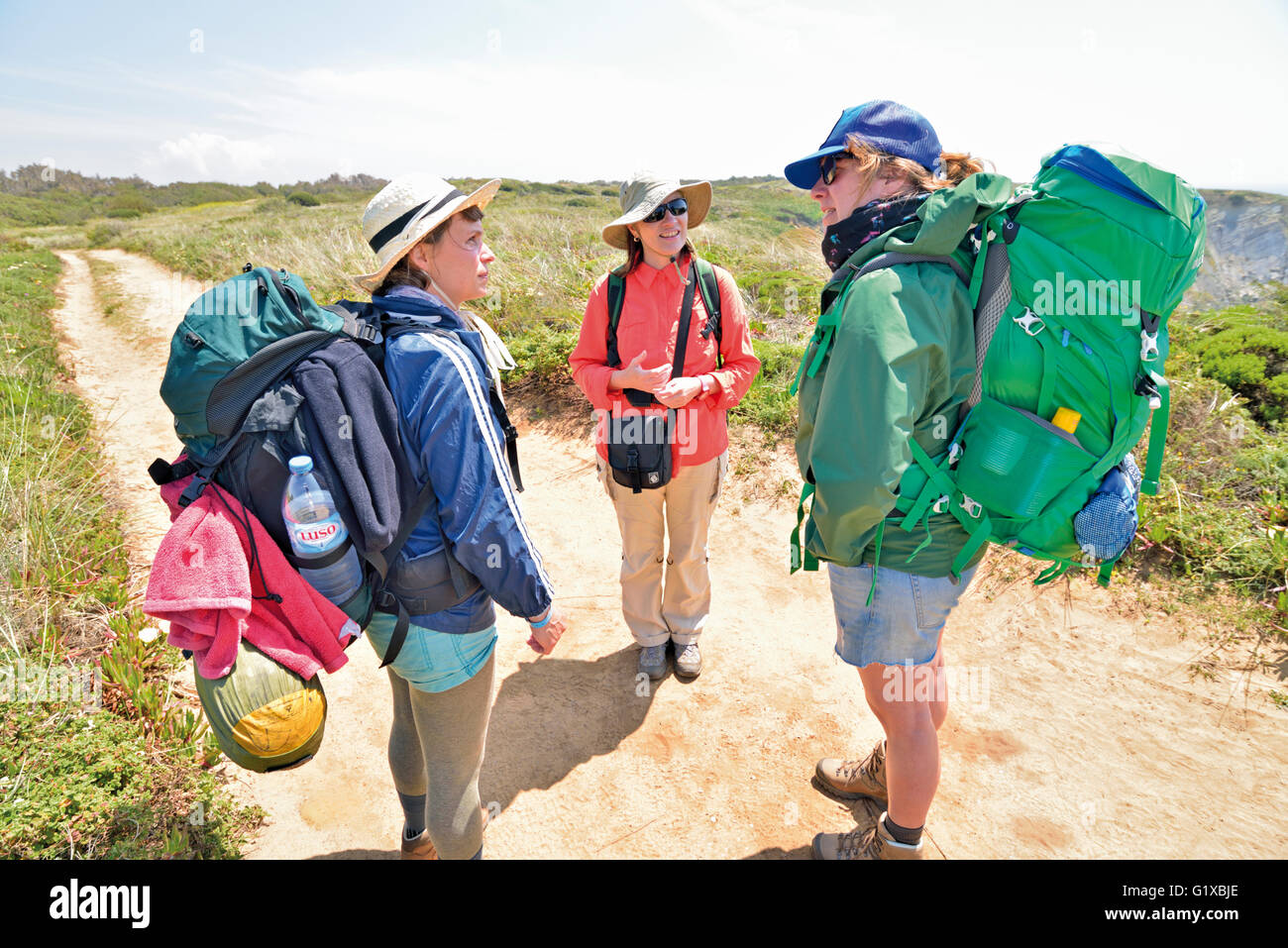 Portugal, Alentejo: Casual meeting of three female walkers on the coastal trail of trekking route Rota Vicentina - Stock Image