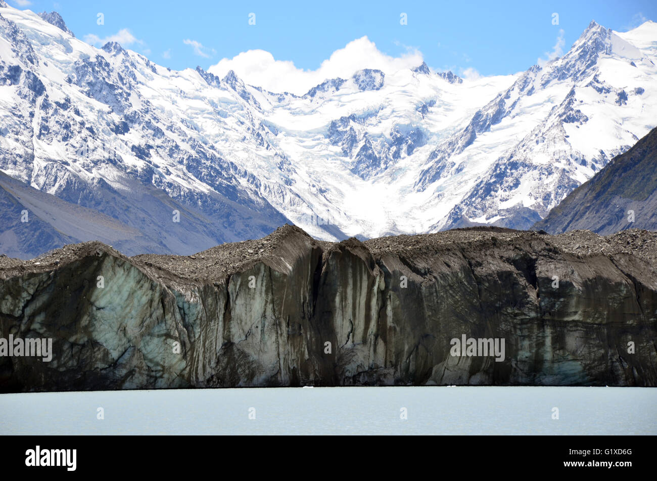 Glacier on a glacial lake at the base of snow covered mountains - Stock Image