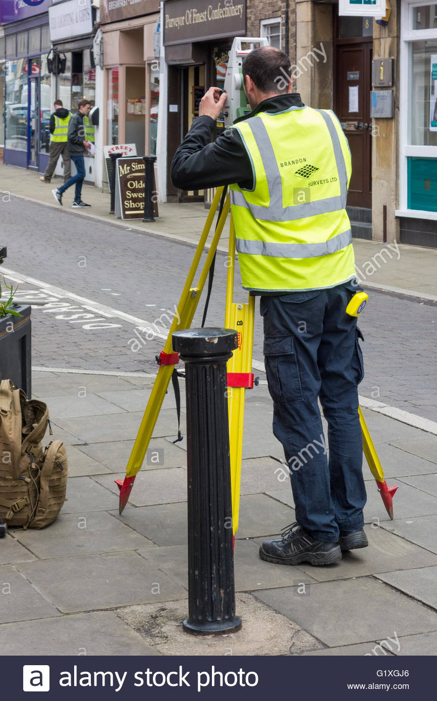 A surveyor carrying out a survey in the Ely High Street - Stock Image