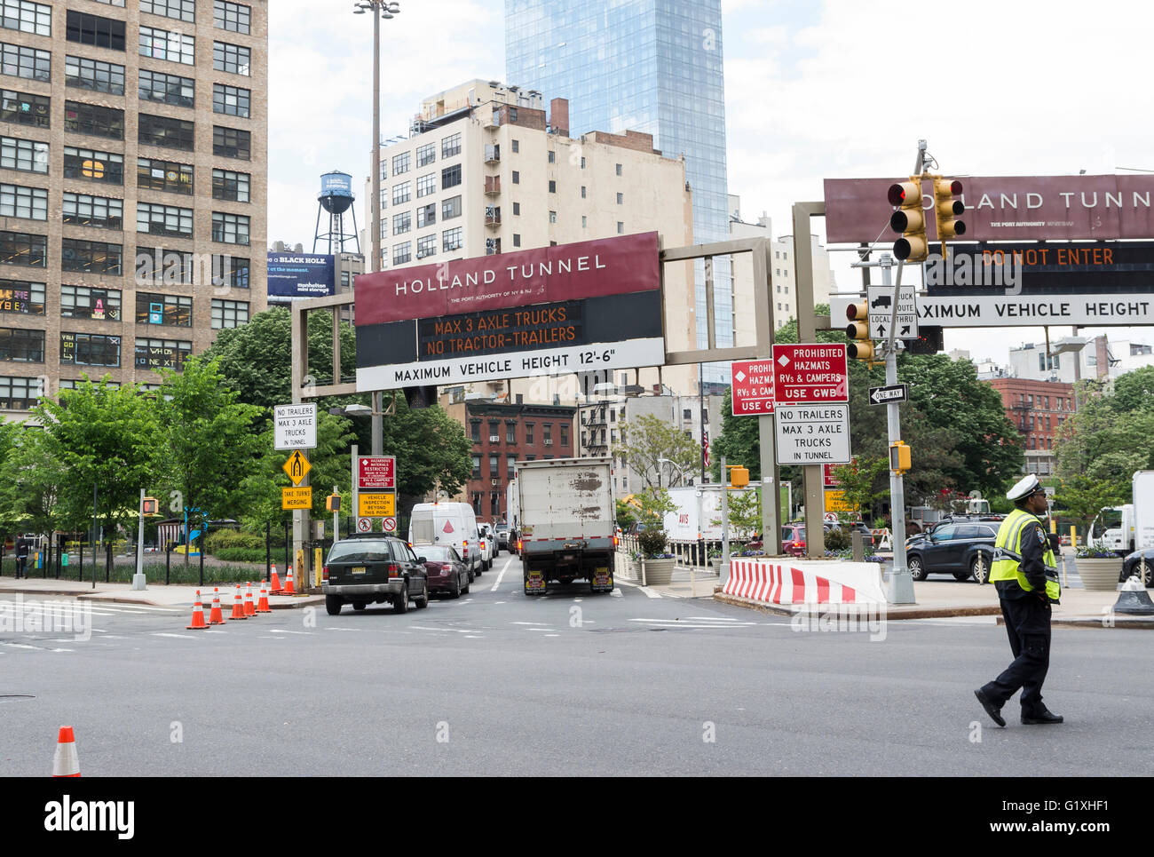 Entrance to Holland Tunnel Hudson River crossing in Manhattan at Canal Street with traffic cop directing traffic - Stock Image