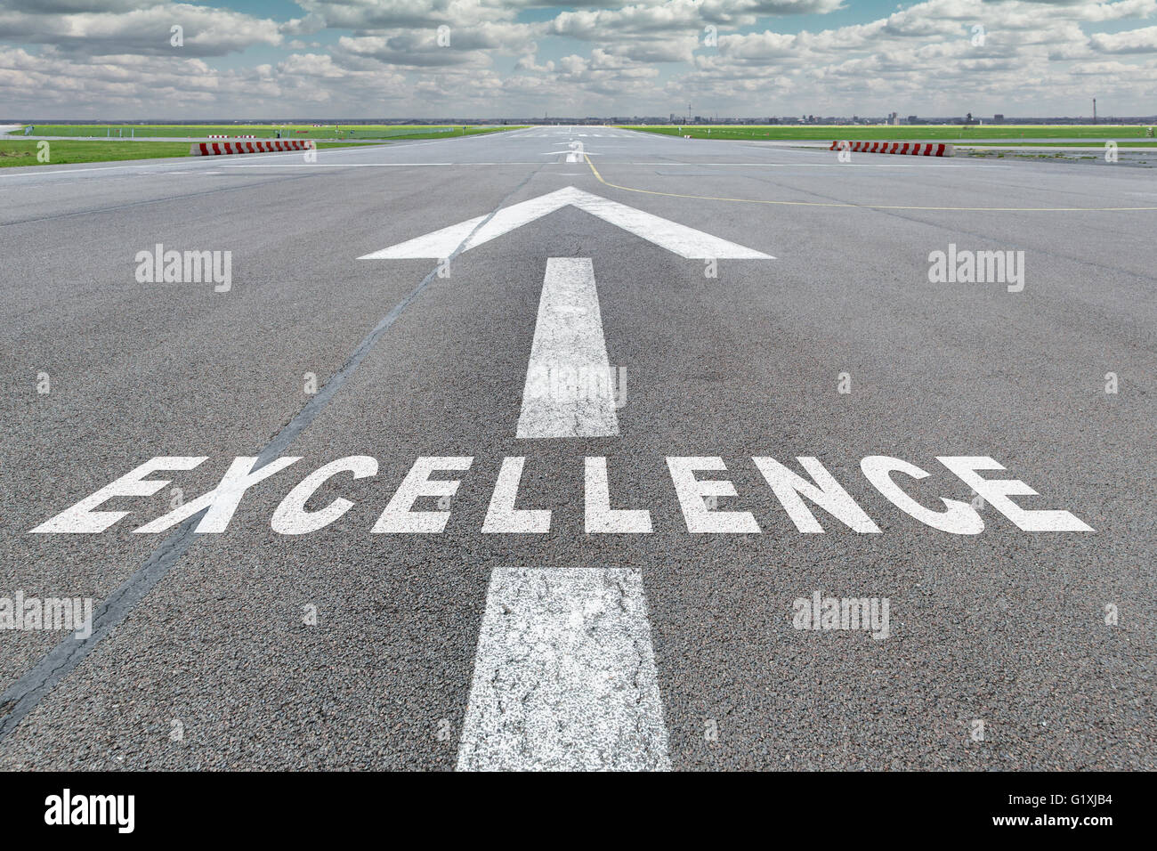 Runway of airport with arrow guideline and Excellence letters painted on the surface - Stock Image
