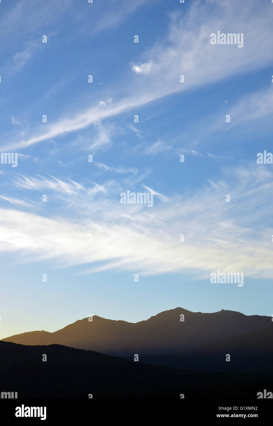 Zigzag cloud patterns in the sky above mountains at dusk - Stock Image
