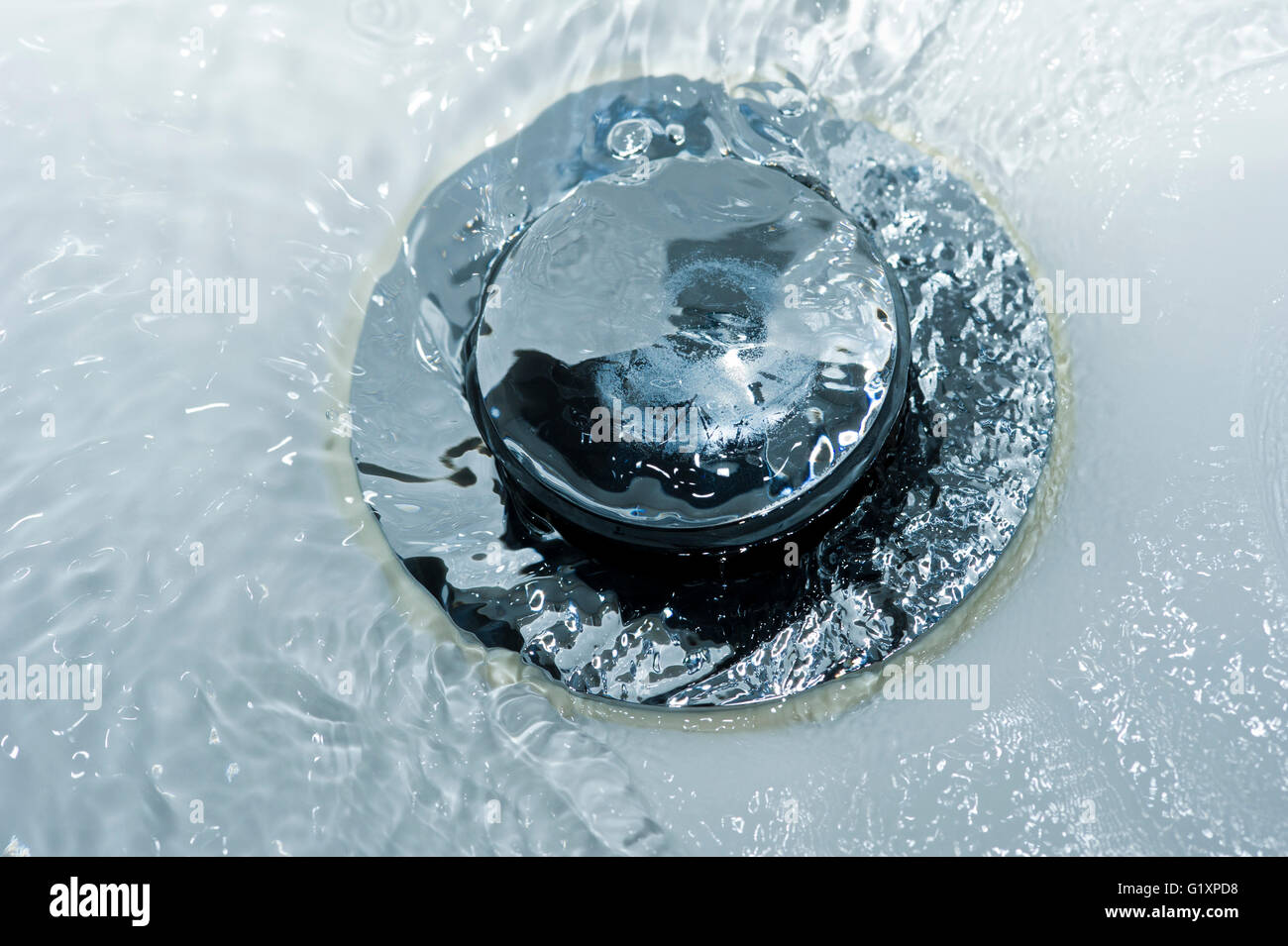 Water pouring down a sink plughole - Stock Image