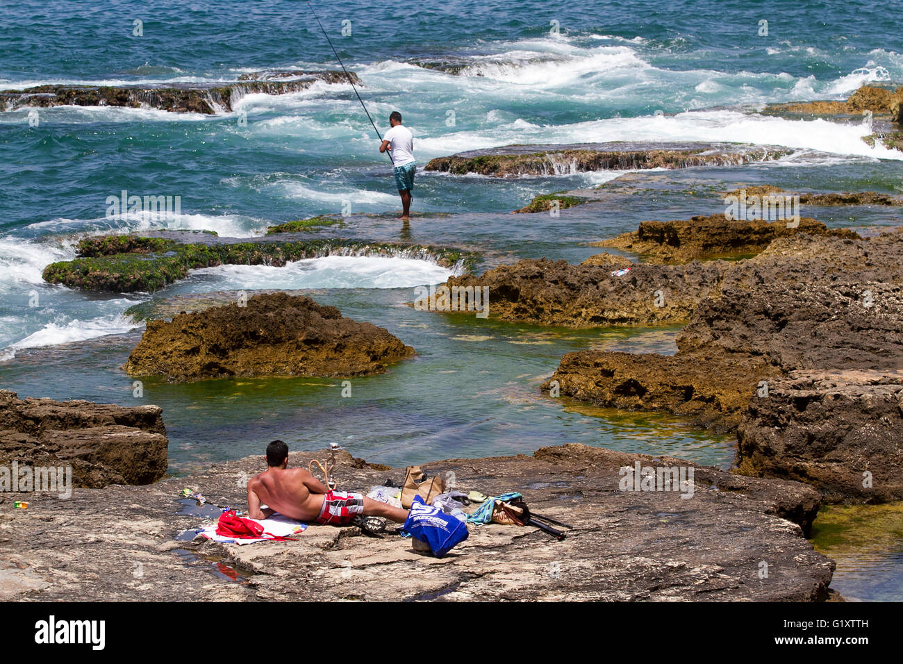 Beirut Lebanon, 20th May 2016. A sunbather enjoys the sun on the seafront rocks as Beirut swelters in high temperatures - Stock Image
