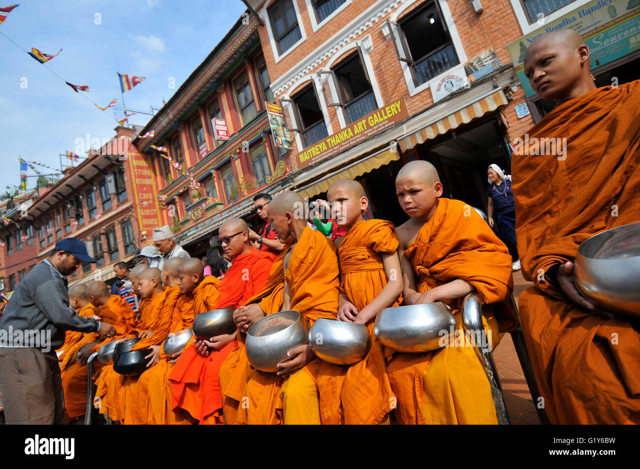Devotees offering holy grains and money to Buddhist monks at