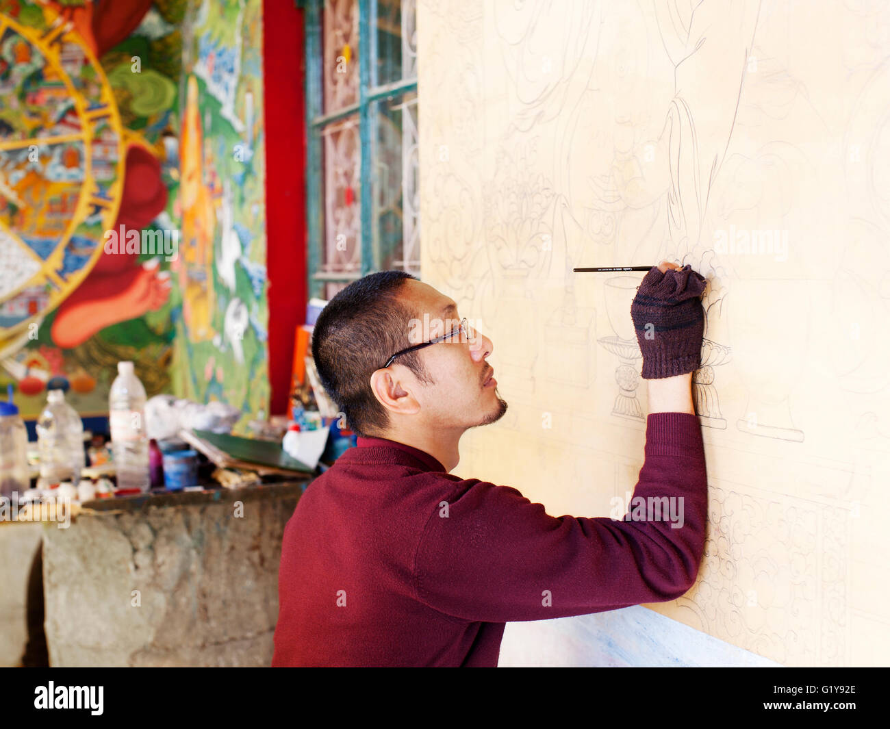 A Tibetan monk paints a mural on a wall at the entrance to the Tibetan Library of Works and Archives. - Stock Image