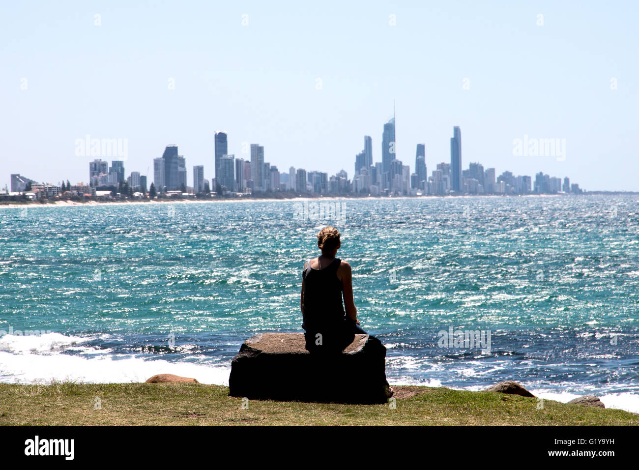 Woman sitting on rock looking across to the high rise buildings of the Gold Coast in Queensland Australia - Stock Image