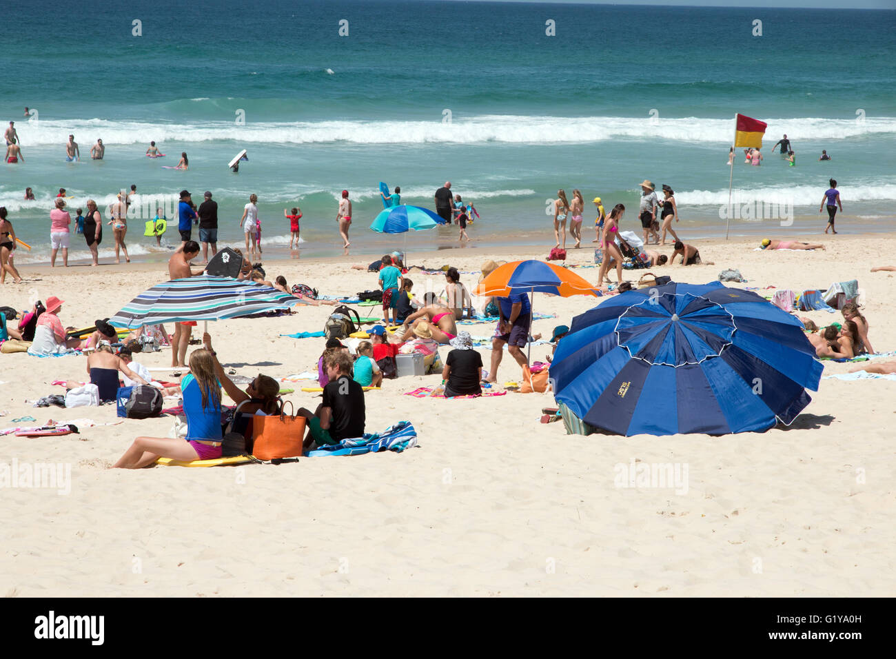 People enjoying the beach and warm weather on the Gold Coast in Queensland Australia - Stock Image