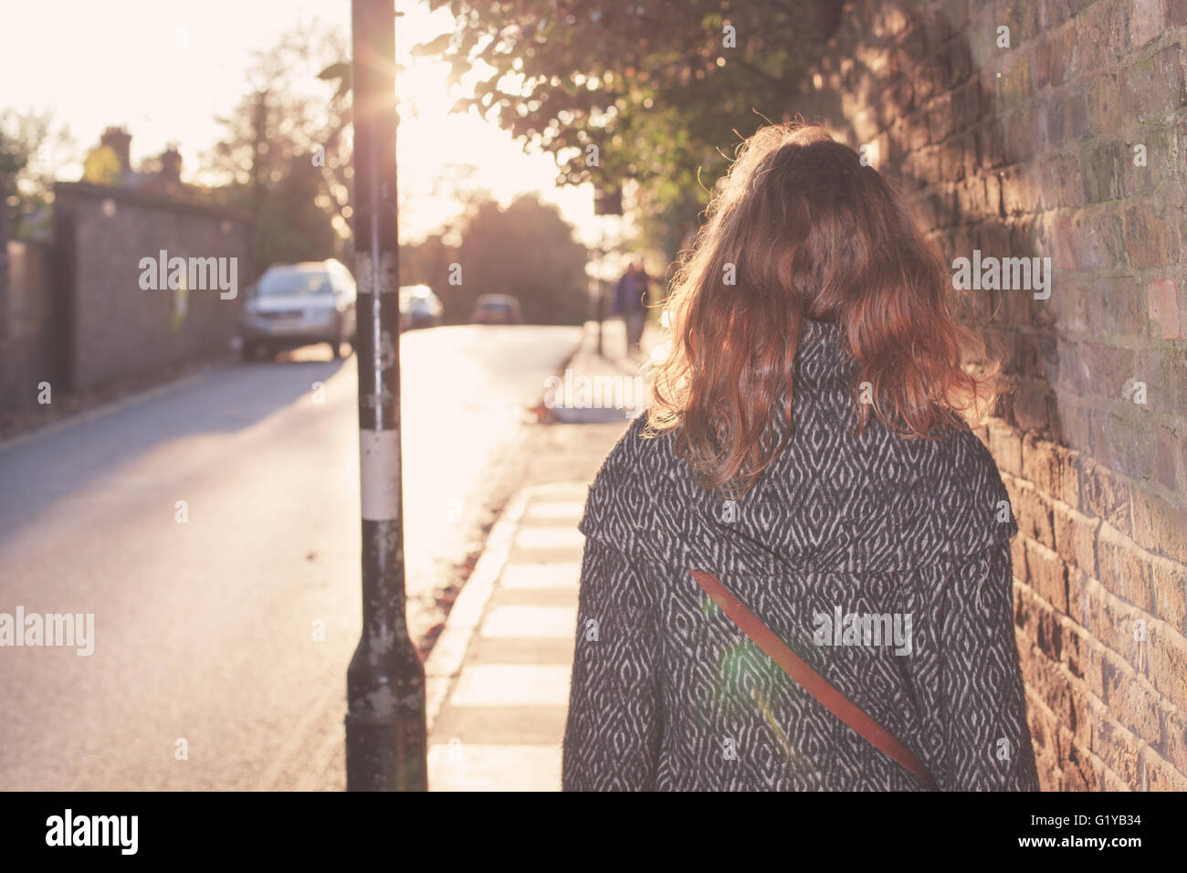A young woman is walking into the sunset on an autumn day in the city - Stock Image