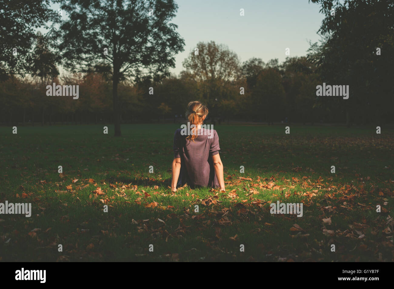 A young woman is siting on the grass in the park in the evening - Stock Image