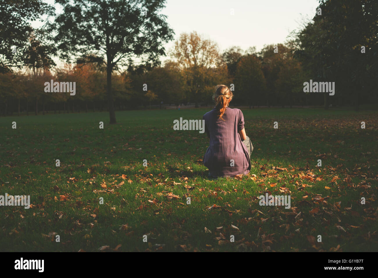 A young woman is siting on the grass in the park in the evening Stock Photo