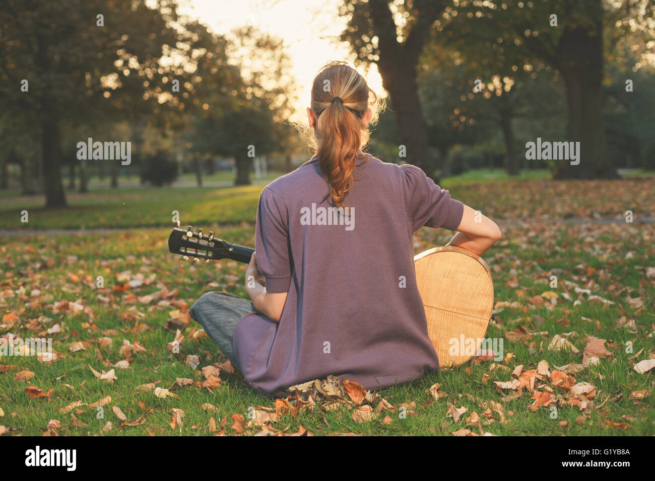 Rear view of young woman sitting on the grass and playing guitar in the park at sunset - Stock Image