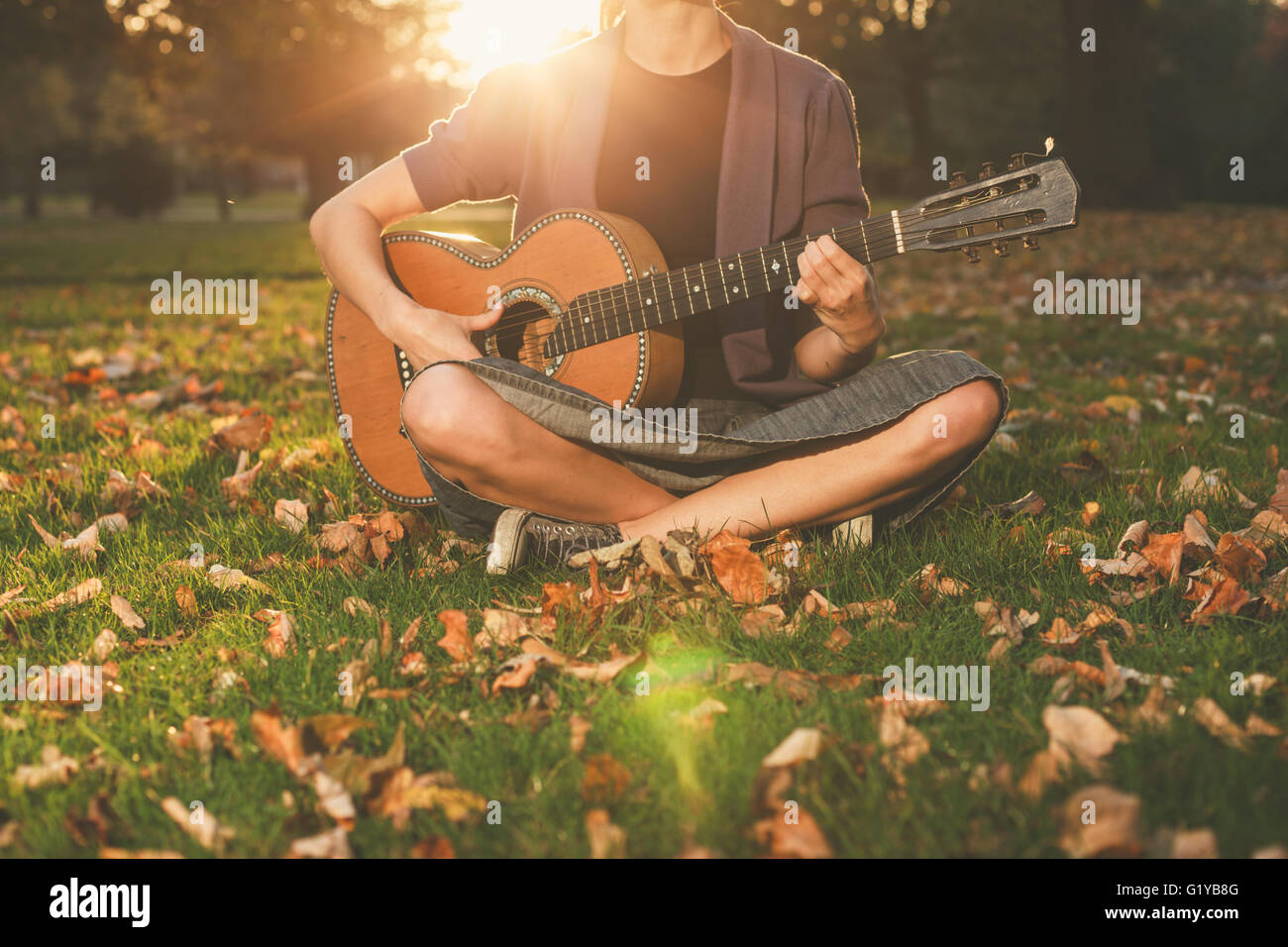 A young woman is sitting on the grass in the park and is playing guitar at sunset - Stock Image