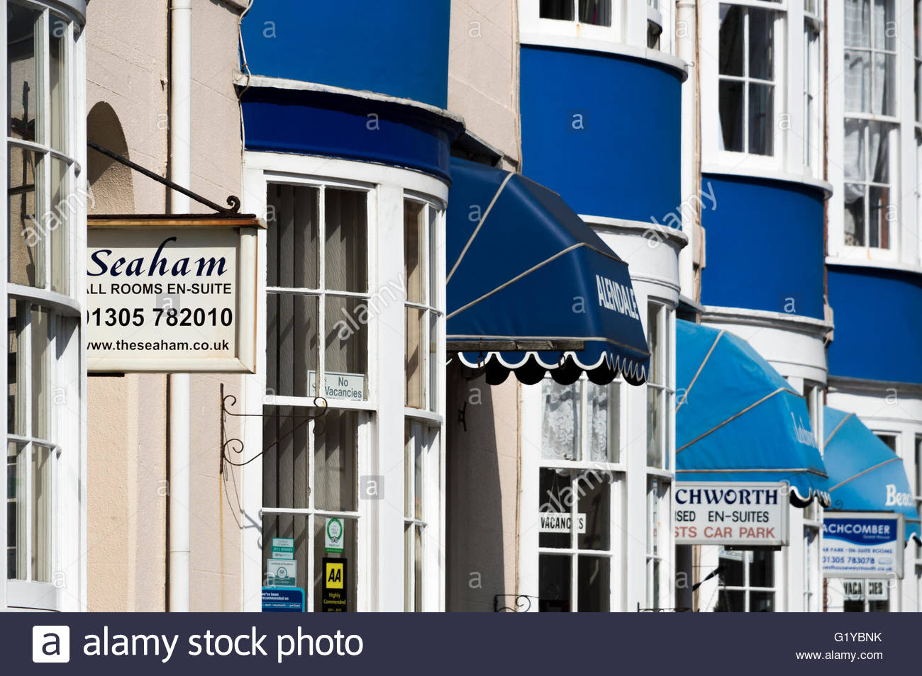 Looking along a row of terraced houses, Bed and Breakfast accommodation with round bay windows and canopies - Stock Image