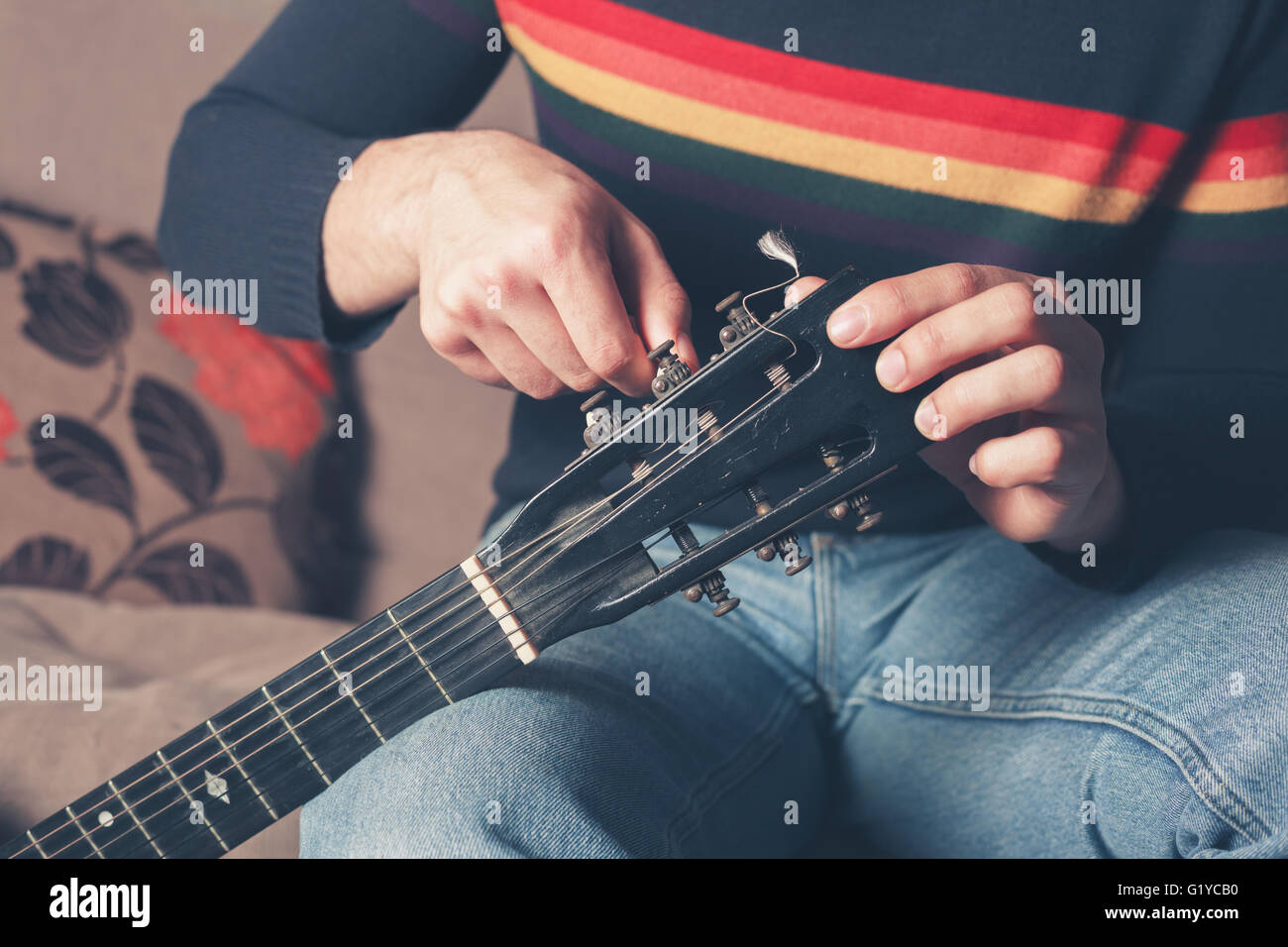 A young man is sitting on a sofa and is tuning a guitar - Stock Image