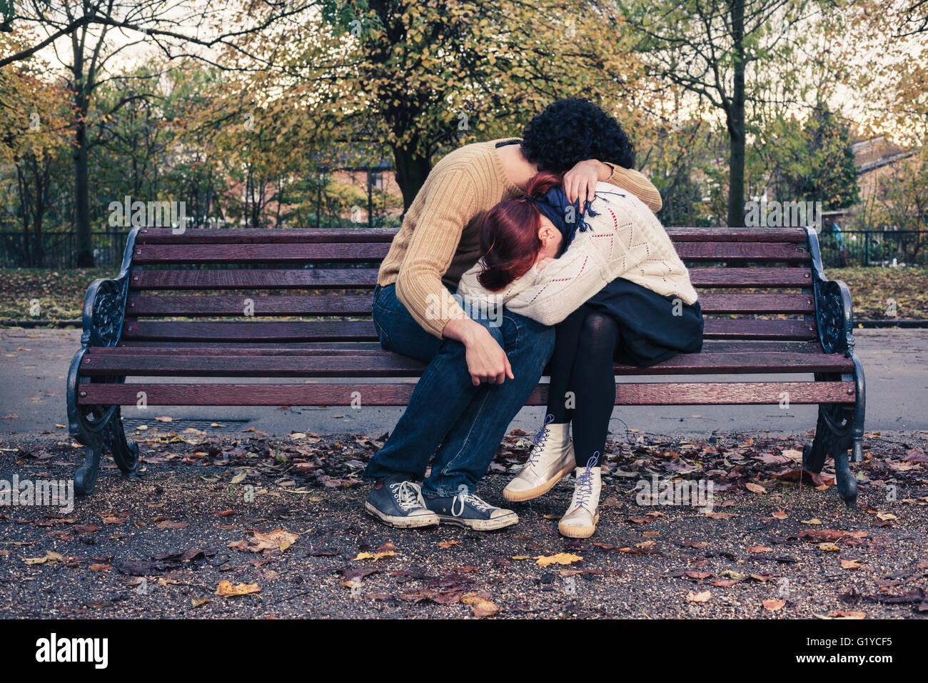 A sad young couple is embracing on a park bench in autumn - Stock Image