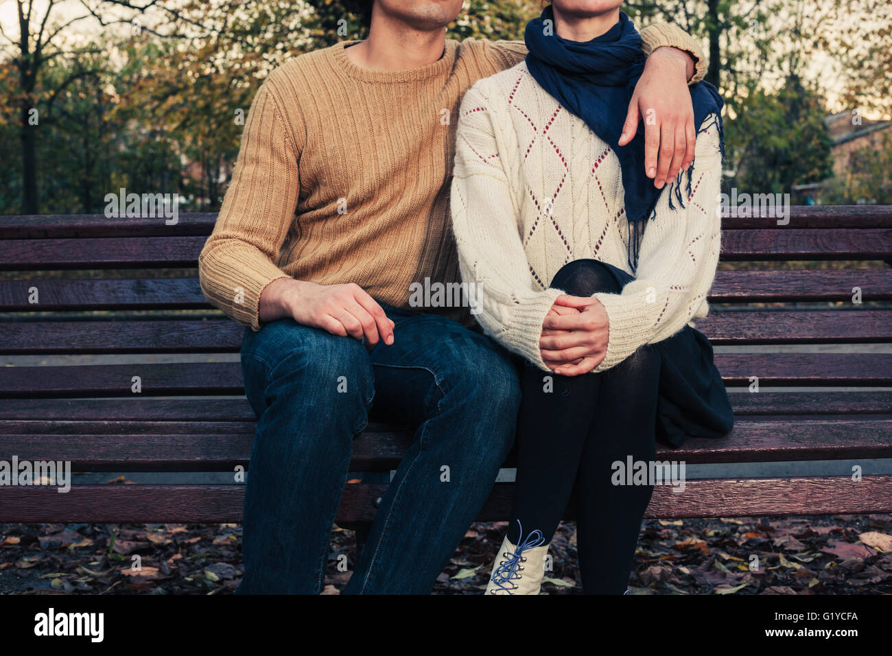 A young couple is sitting and holding each other on a park bench in autumn - Stock Image