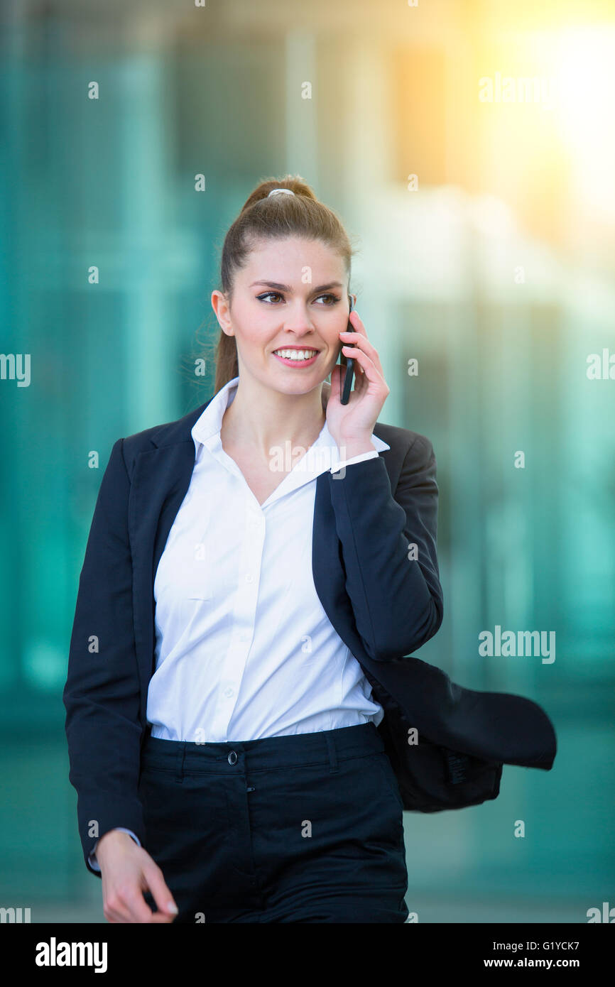 Businessman talking on mobile phone in financial district - Stock Image
