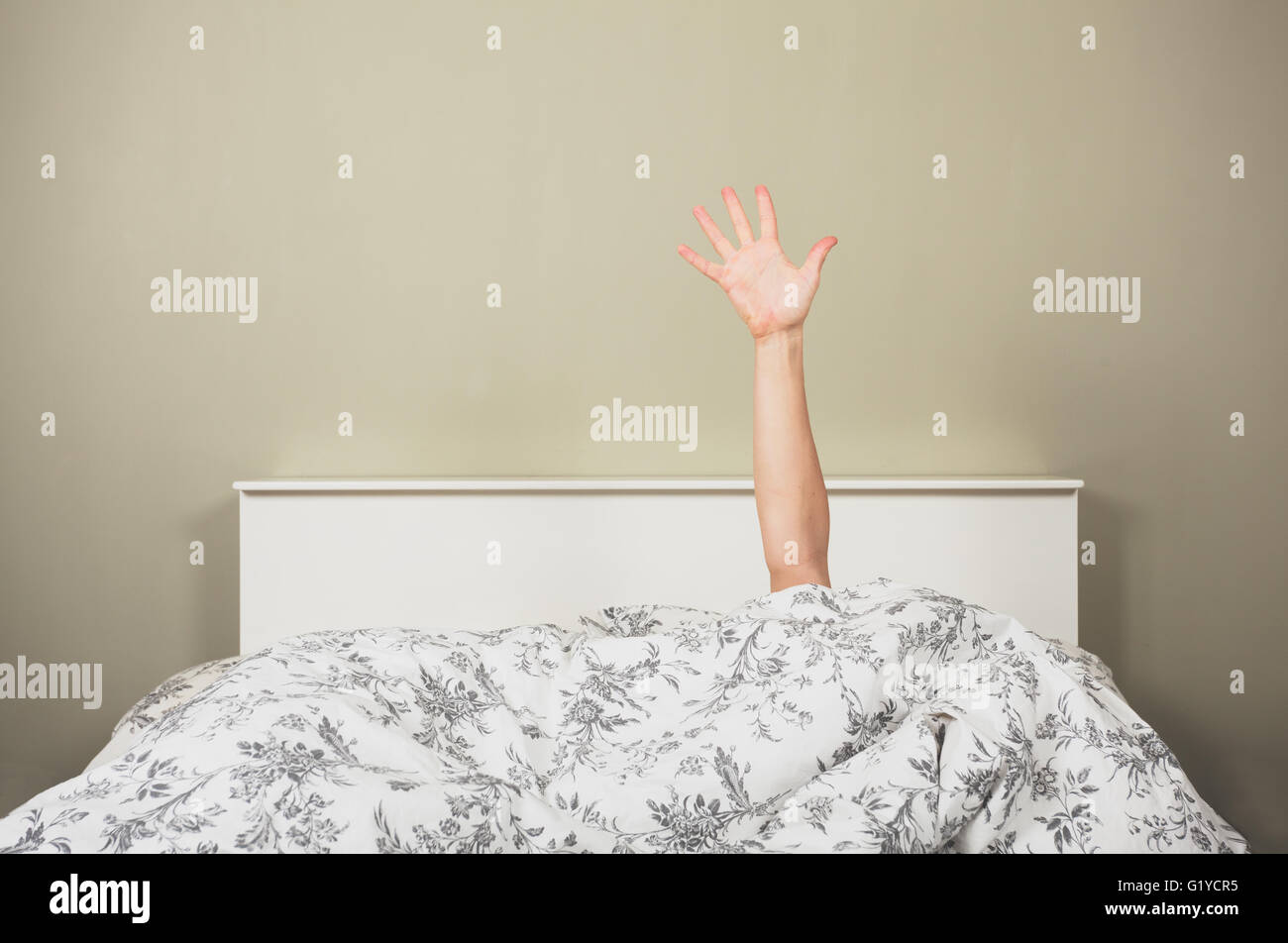 A woman is waving from under the covers in a bed - Stock Image