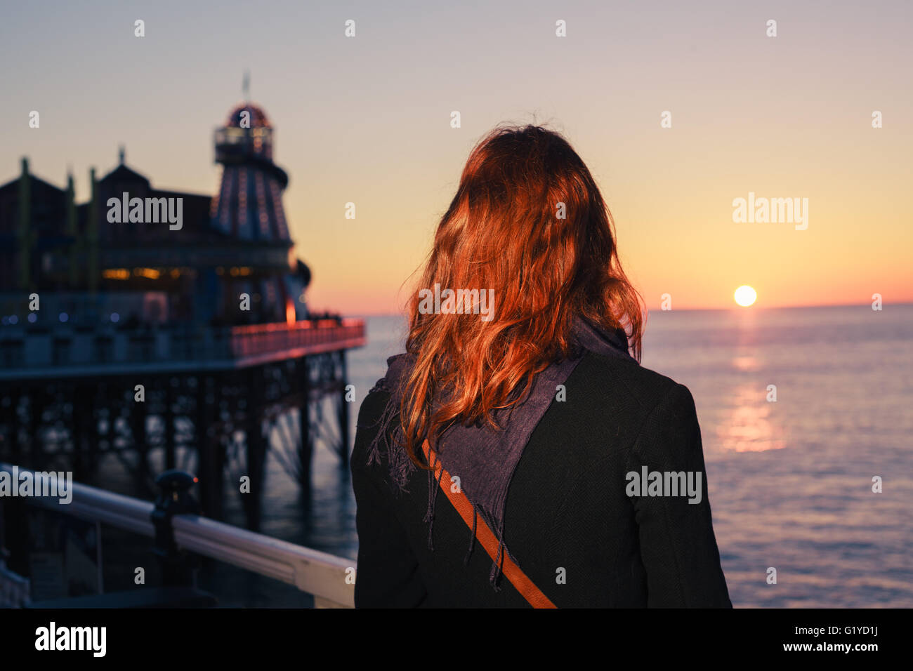 A young woman is walking on the coast at sunset and is admiring the sea - Stock Image