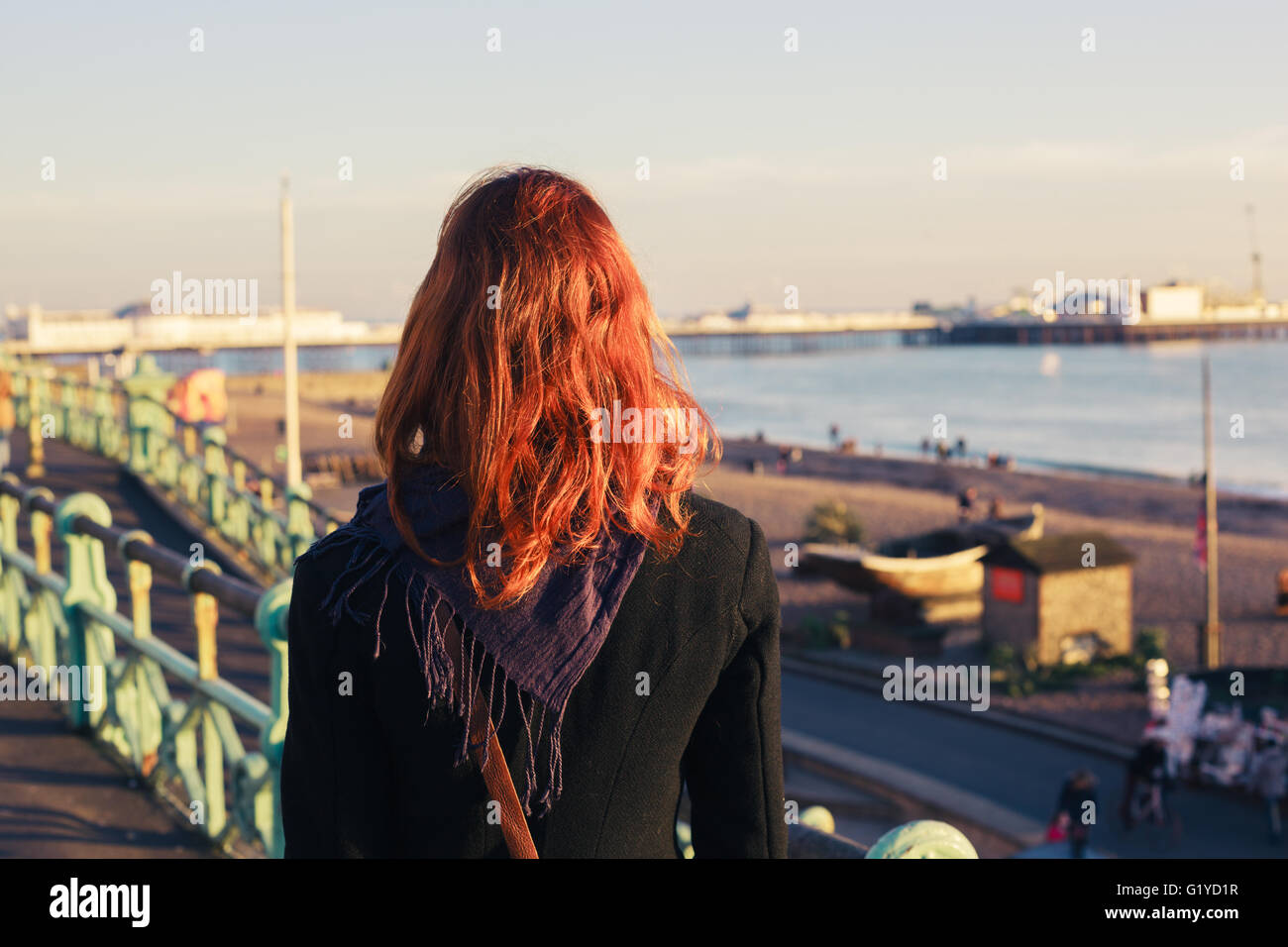 A young woman is walking on the coast at sunset and is admiring the sea Stock Photo