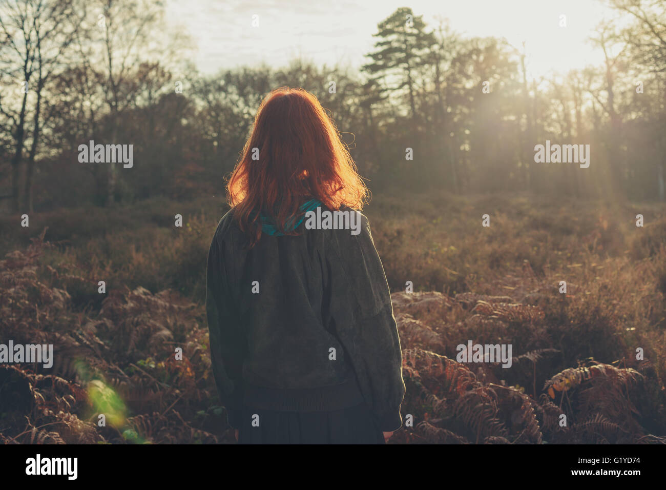 A young woman is standing in a forest at sunset Stock Photo