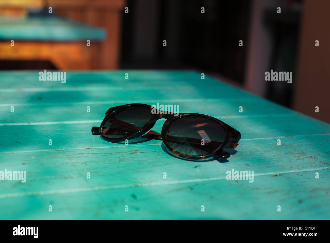 A pair of sunglasses on a blue table in the sunlight - Stock Image