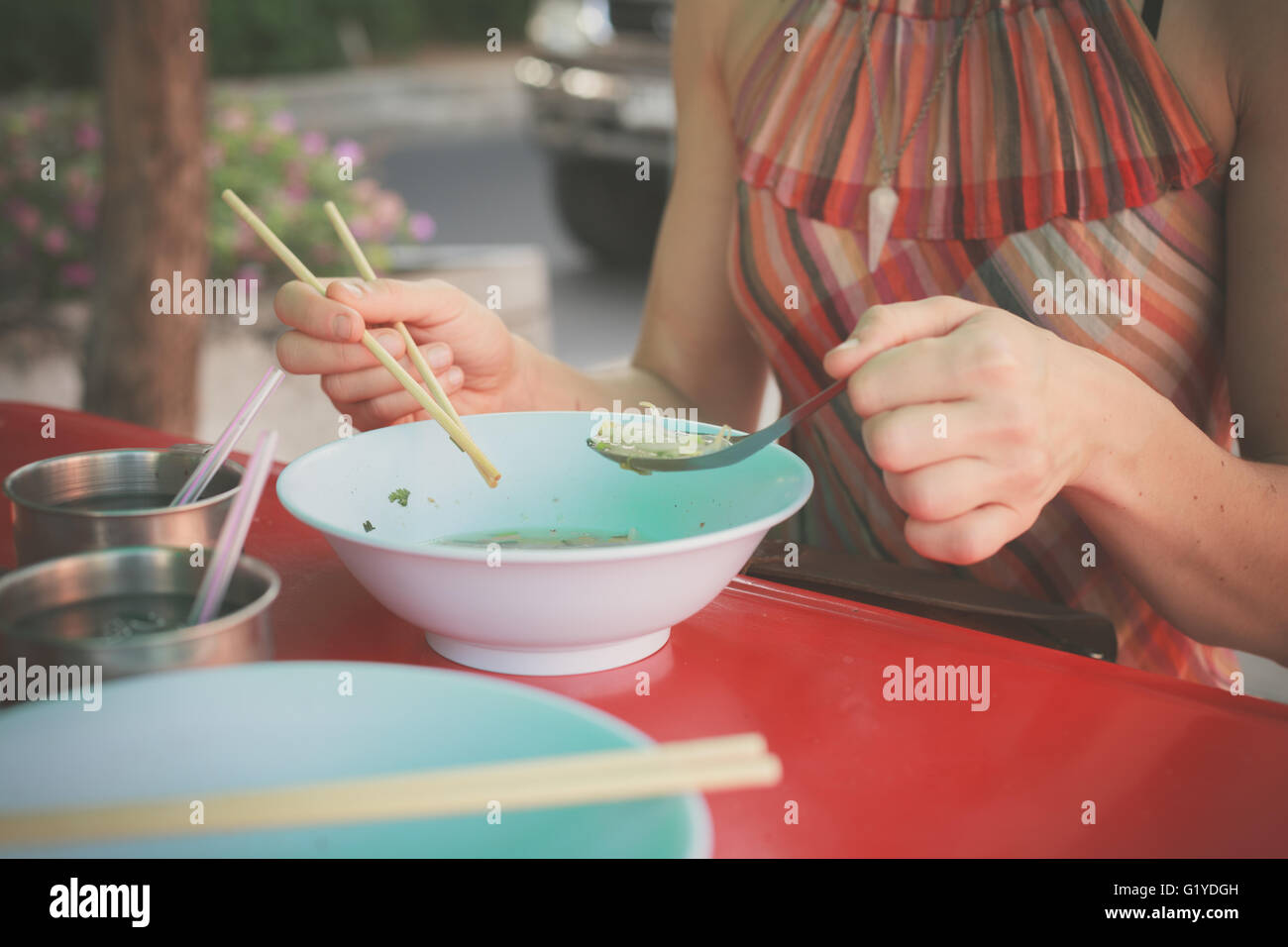 A woman is sitting at a table in the street and is eating noodles - Stock Image