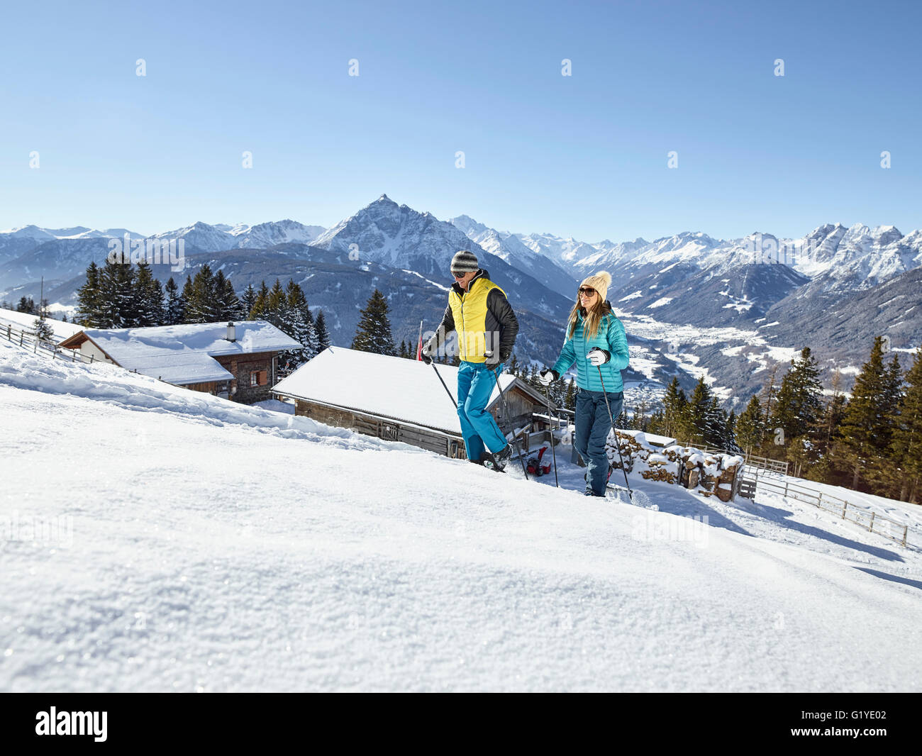 Woman and man, couple hiking with snowshoes in a snowy landscape, Patscherkofel, Patsch, Innsbruck, Tyrol, Austria - Stock Image
