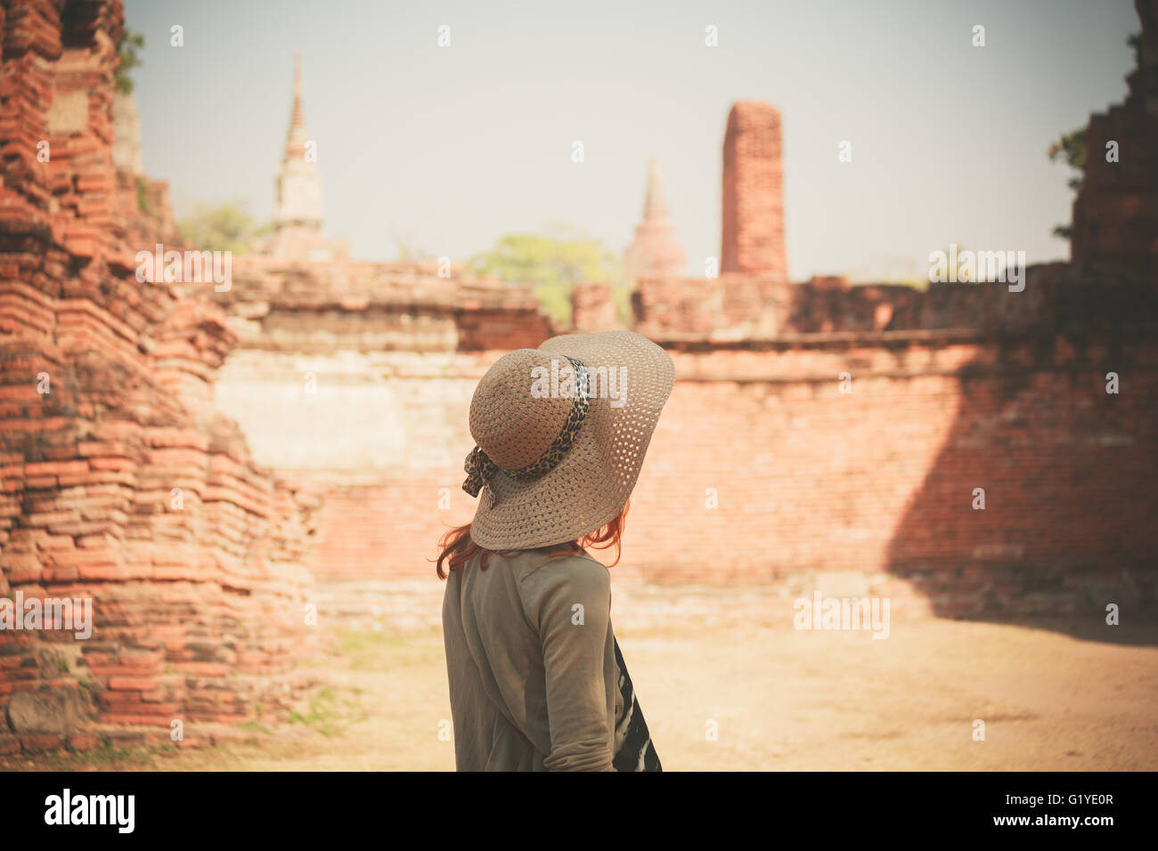 A young woman is exploring the ancient ruins of a buddhist temple city - Stock Image