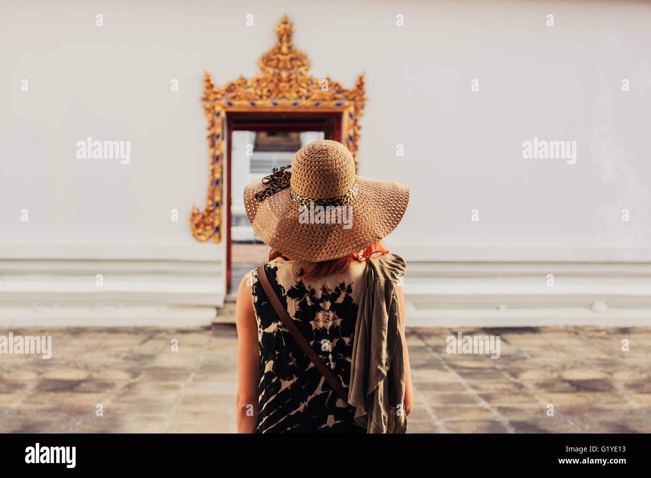 A young woman is looking at the elaborate entrance to a buddhist temple - Stock Image