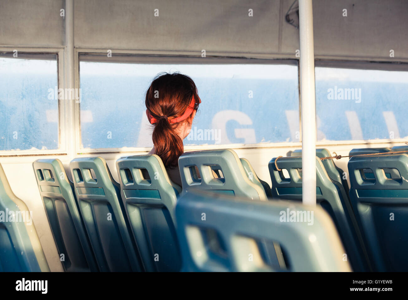 A young woman is sitting by herself on a ferry - Stock Image
