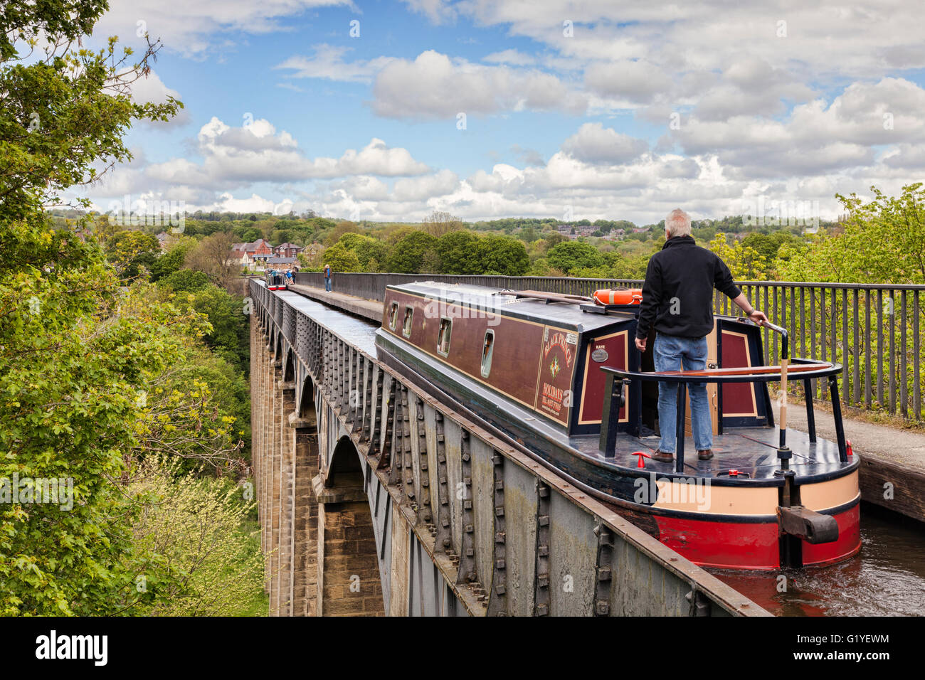 Man with his hand on the tiller, steering narrowboat over the Pontcysyllte Aqueduct, built by Thomas Telford, on - Stock Image