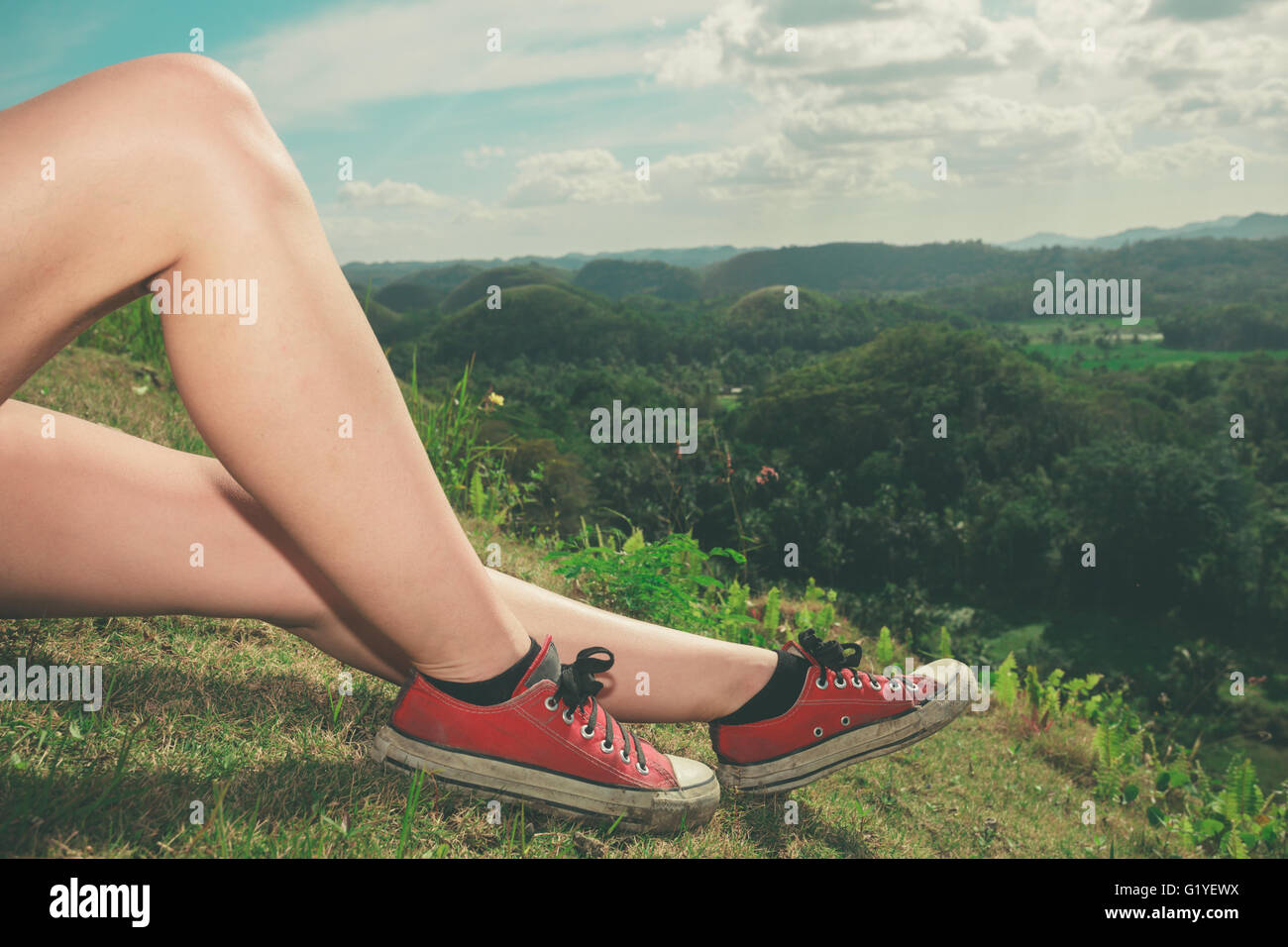 The legs of a young woman as she is relaxing on a hill in the tropics - Stock Image