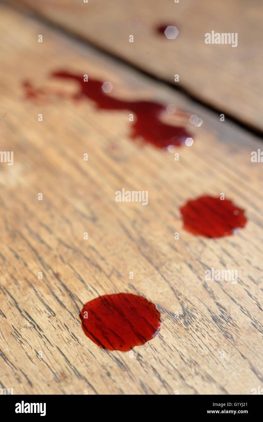 Vivid blood drops on wooden oak floor - Stock Image