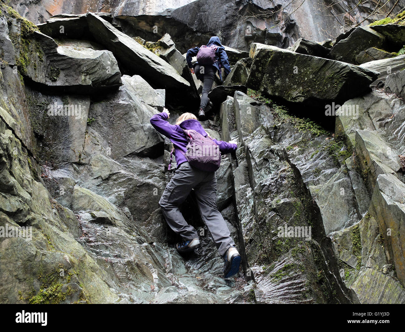 Two children climbing rocks in an Cathedral quarry, Cumbria - Stock Image