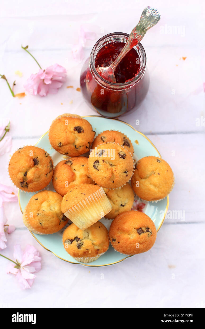 Rustic wooden breakfast background with fresh muffins and blooming cherry flowers - Stock Image