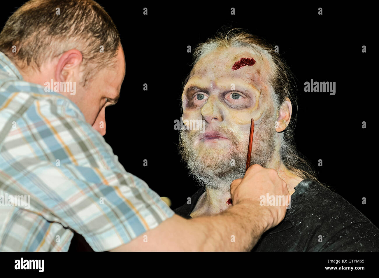 A special effects makeup artist applies latex prosthetics and fake wounds to a male actor at