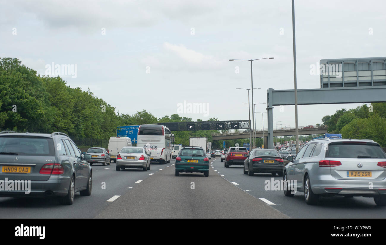 Slow traffic on the western stretch of the M25 approaching Heathrow anticlockwise, National Express bus in queue - Stock Image