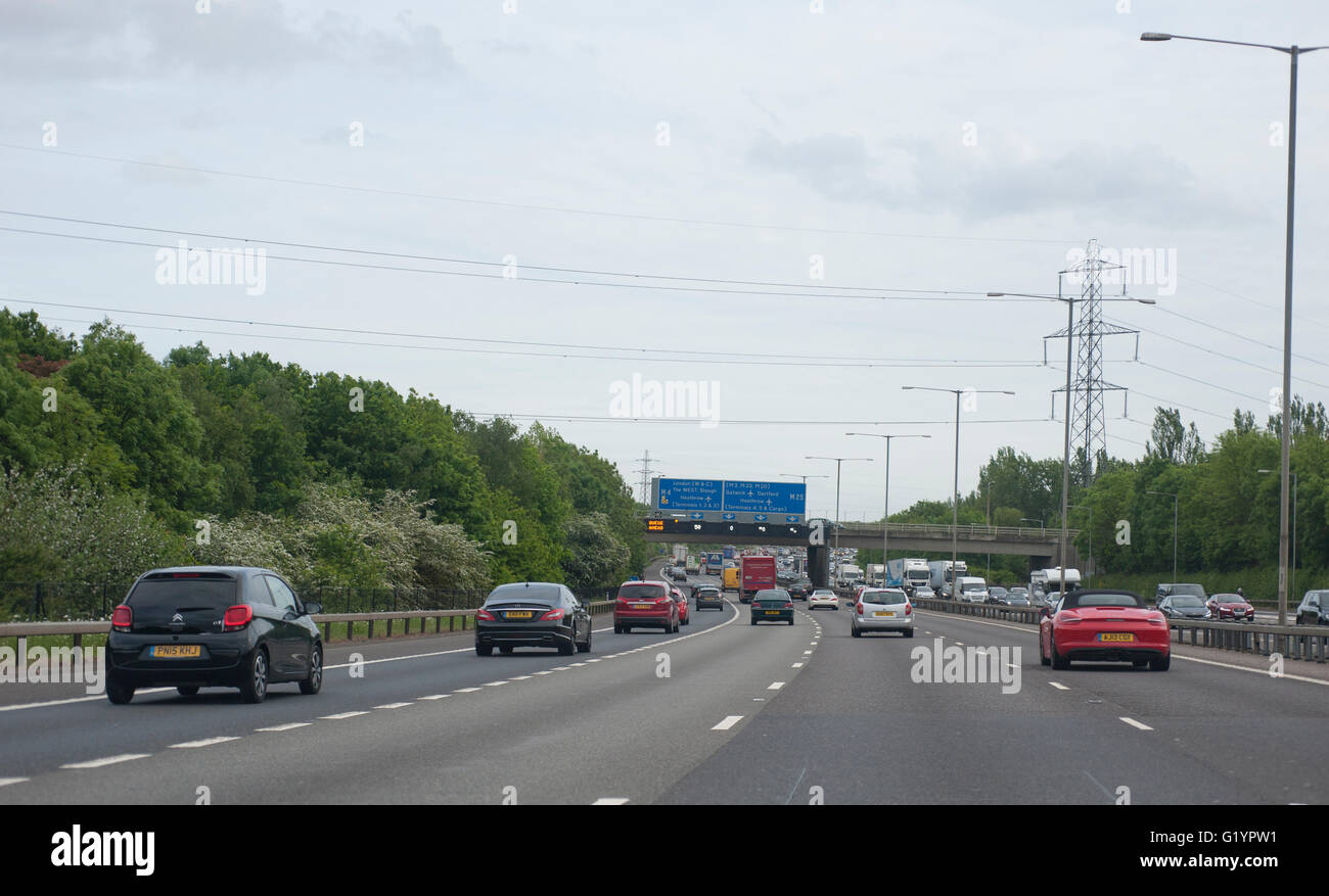 Slow traffic on the western stretch of the M25 approaching Heathrow anticlockwise, overhead gantry sign with Queue - Stock Image