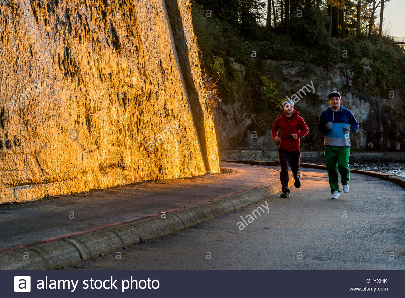 Joggers, Stanley Park seawall at sunset, Vancouver, British Columbia, Canada - Stock Image