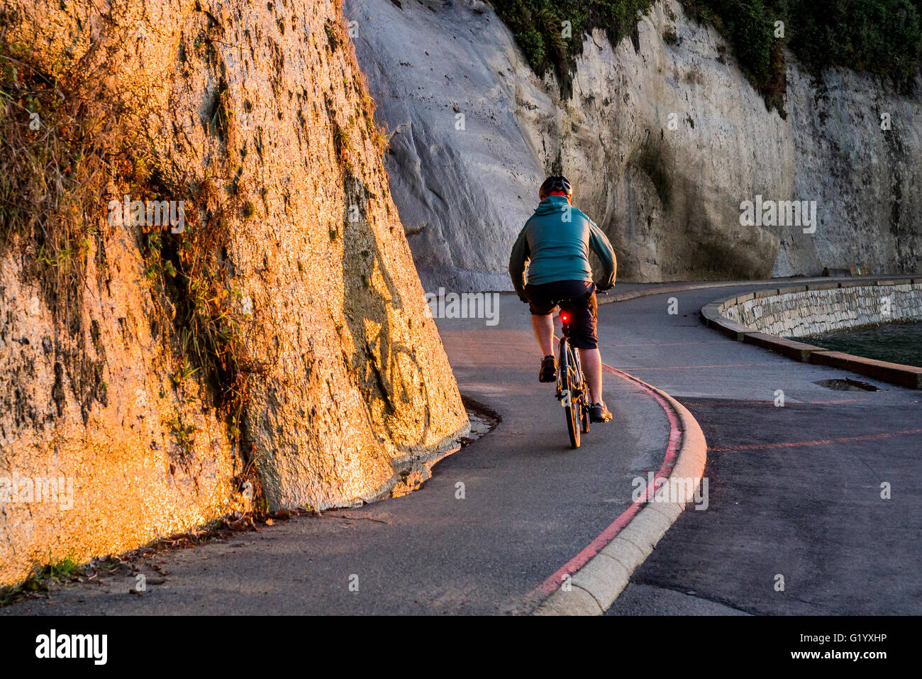 Bicyclist, Stanley Park seawall at sunset, Vancouver, British Columbia, Canada - Stock Image
